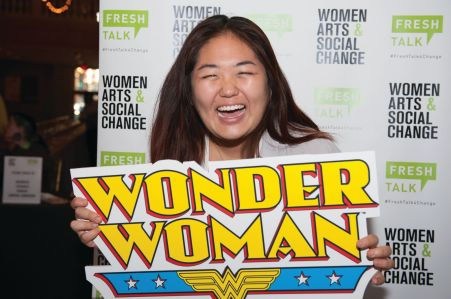 A woman stands with a Wonder Woman sign laughing at someone off camera.