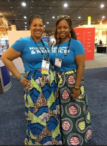 "Two people posing for a portrait wearing t-shirts that say ""Museums & Race,"" African print skirts, and conference badges."