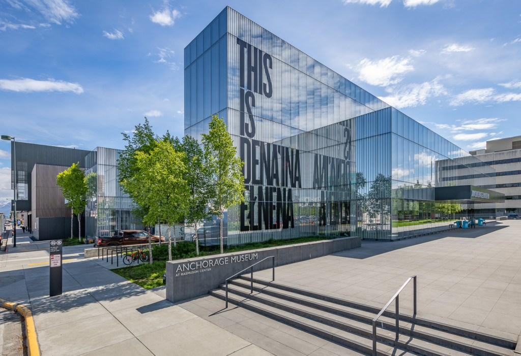 "A glass building facade with large letters reading ""This is Dena'ina Elnena"""