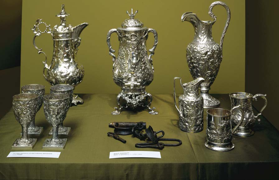 A group of silver teapots and service with a pair of iron shackles displayed between them.