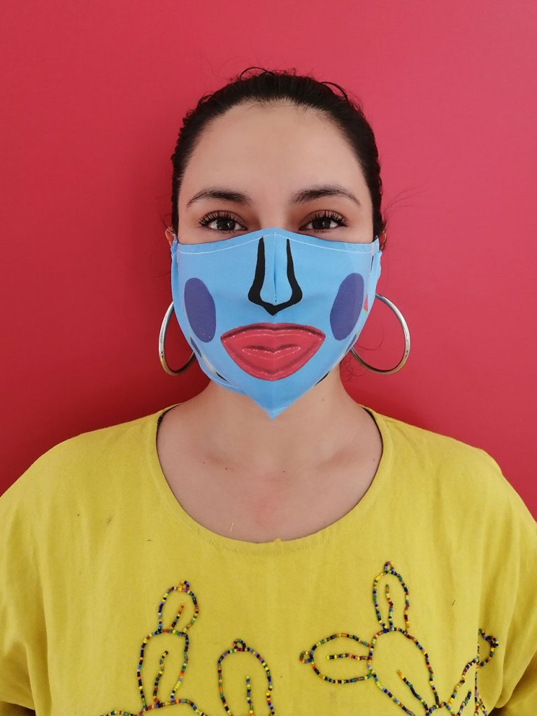 Photo of a person wearing a blue face mask with a stylized nose, lips, and cheeks drawn on it