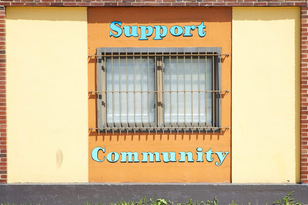 "A colorful wall and window with the message ""Support Community"" painted on it"