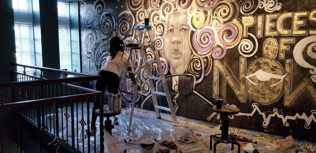 "An artist painting a mural indoors of a figure with an abstract swirl of hair and the title ""Pieces of Now."""