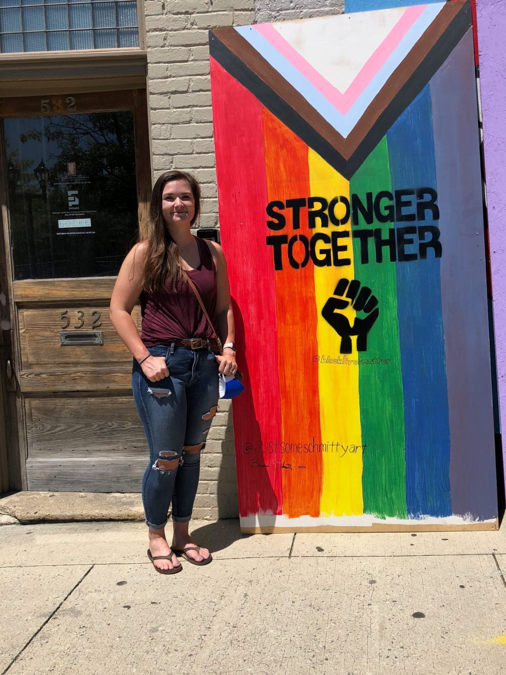 "A person standing in front of a mural reading ""Stronger Together"" with a Black power fist against an inclusive Pride flag backdrop"