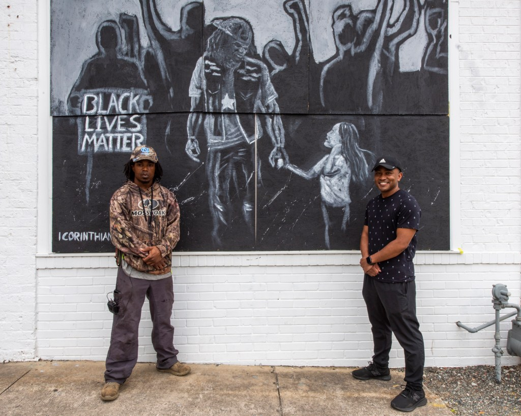 Two people standing in front of a mural depicting a Black Lives Matter protest