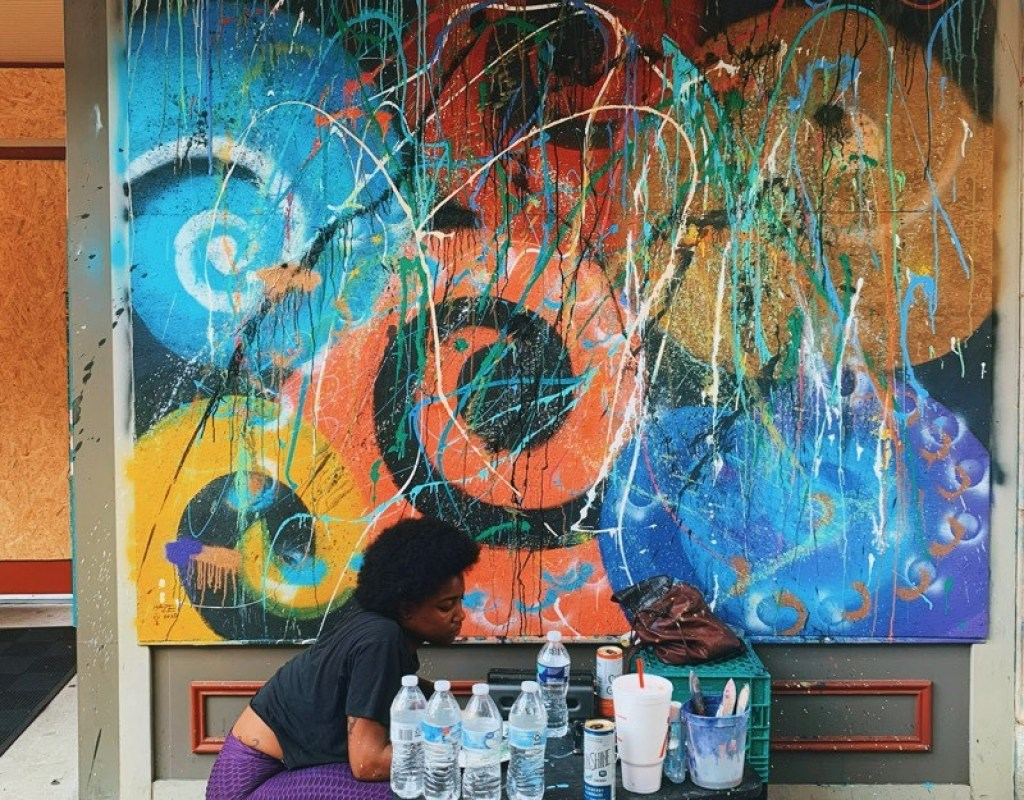 An artist in front of an abstract mural of swirling forms, drips, and slashes
