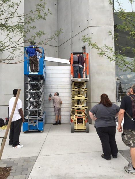 A team of workers stacking metal rods as a barrier in front of a building