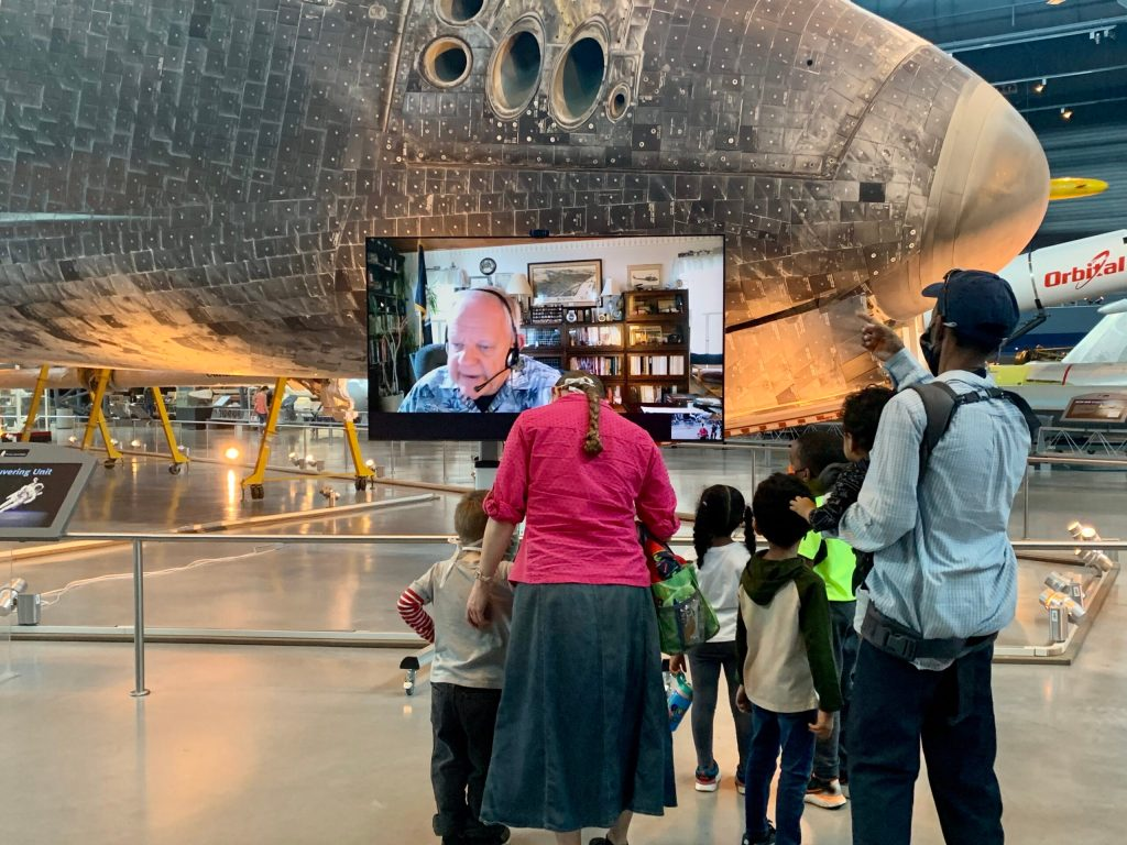 Adults with children in front of a video screen with a docent explaining an artifact plane in the background