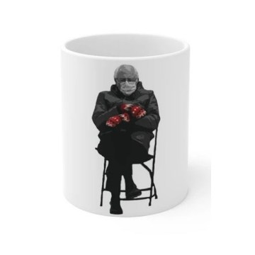 A rendering of a white mug with an image of Bernie Sanders sitting in a folding chair with his arms crossed, wearing mittens and a surgical mask