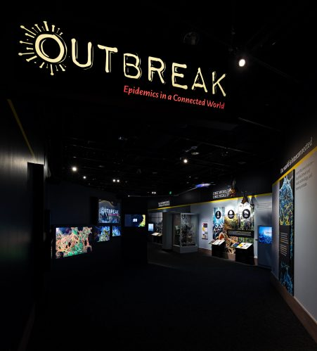 Dark lighted entrance to Outbreak exhibit with multiscreen video and displays in distance