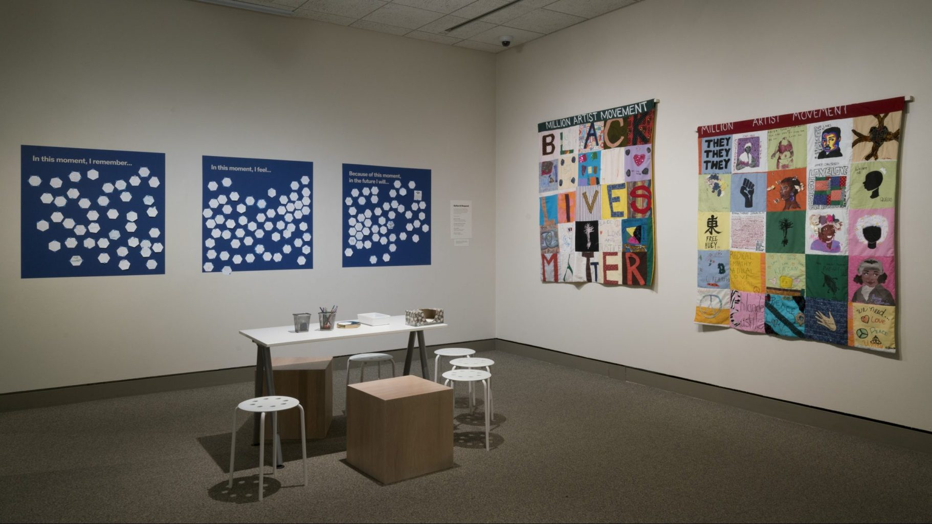"""A museum gallery space with Black-Lives-Matter-themed art and a workstation for answering questions on poster boards: """"In this moment, I remember...,"""" """"In this moment, I feel...,"""" and """"Because of this moment, in the future I will..."""""""