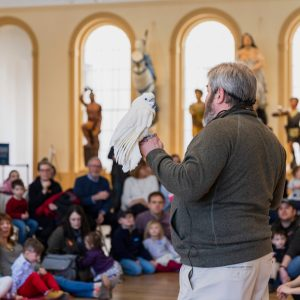 A speaker addressing an audience inside a museum with a bird perched on his hand