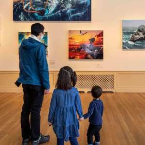 One adult and two children visitors looking at a gallery wall of paintings depicting fantastical shipwrecks