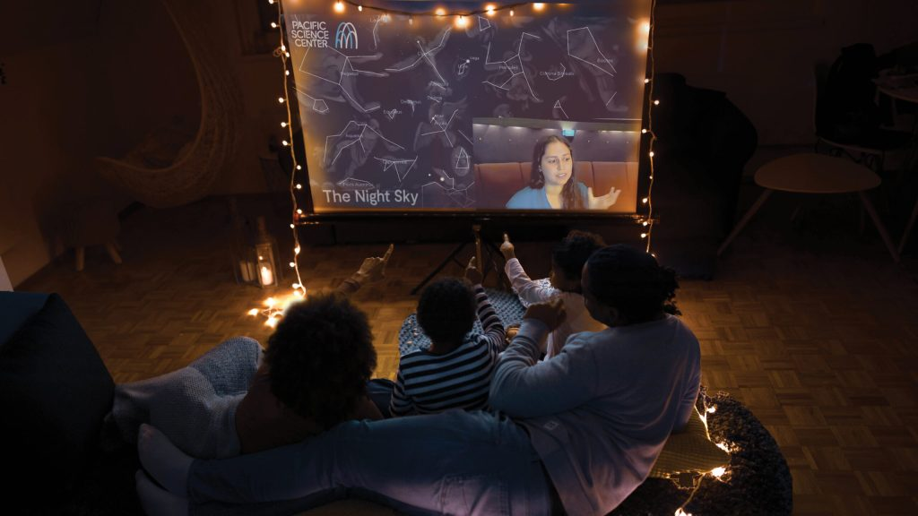 A group of small children and adults watching a Pacific Science Center virtual program on a projector in a darkened room with fairy lights.