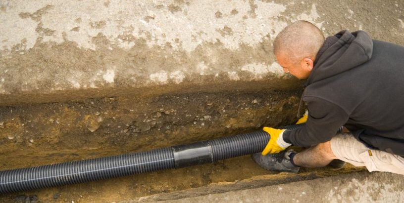Shot of a road worker fitting drain pipes in a drainage ditch