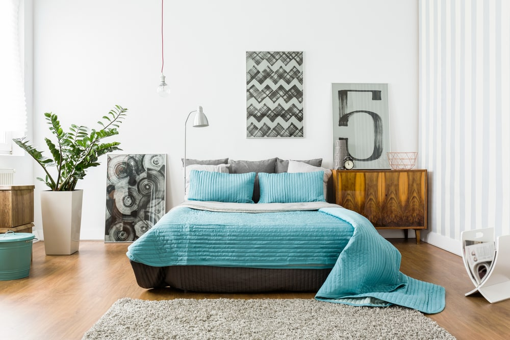 bedroom with gray bed and blue bedspread - 4 questions to ask before your next renovation