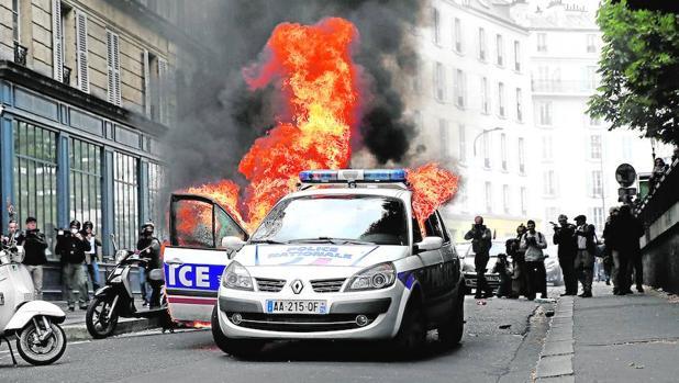 Manifestantes prenden fuego a un coche policial durante una protesta en París