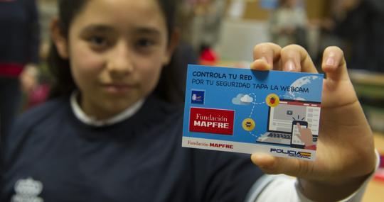 Una alulmna del colegio Sagrado Corazón de Jesús muestra la tarjeta de la Policía y Mapfre para tapar la webcam