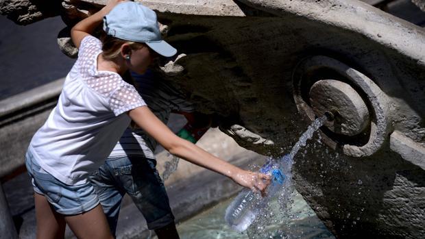 Una persona llena una botella de agua de la fuente de la Piazza di Spagna de Roma