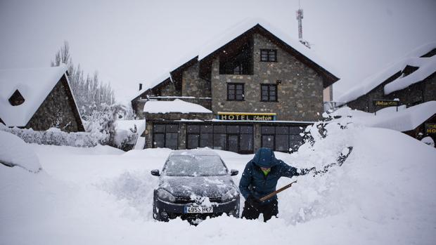 Un hombre intenta desenterrar su coche en Benasque, tras la gran nevada caída en el Pirineo