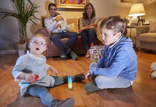 Loreto juega con su hermano Gonzalo mientras sus padres, que sujetan a Mar, los miran