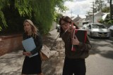 Worthington and Meldrum-Hanna walking in a street with notebooks in arms and Meldrum-Hanna pointing ahead.