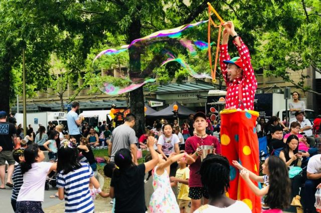 A clown on stilts blows a large bubble while a group of small children look on.