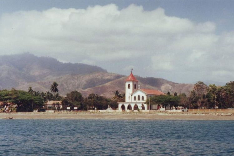 A view from a boat looks across blue water to a red-roofed white Spanish-style church with mountains in the distance.