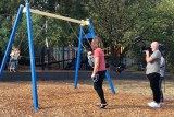 Kate Miller-Heidke and her son are registered while driving the swings