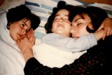 An old family photo of two girls lying in bed cuddling their mother.