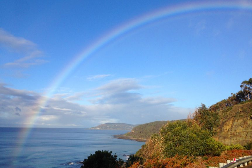 A large rainbow over the ocean on a blue sky day. Two headlands are seen in the distance.