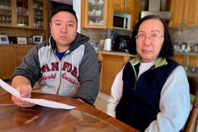 A man in his 30s and woman in her 60s stare ahead at the camera while sitting in their kitchen.