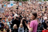 Greta Thunberg in front of a large crowd.