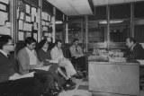 Black and white photo of Hutcheon sitting behind a desk talking to journalists holding notepads and pens.