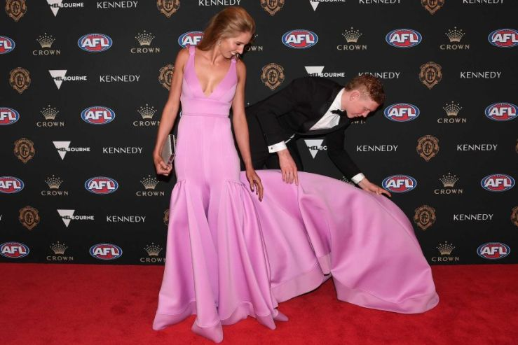 Clayton Oliver leans down to lift the trail of his partner's dress on the Brownlow Medal red carpet