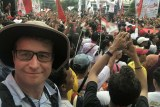 Selfie of Lipson with Widodo and large crowd in background.