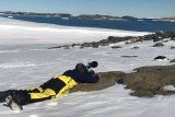 Cameraman lying on rock surrounded by ice filming.