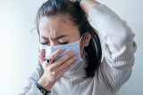 Young woman coughs into face mask.