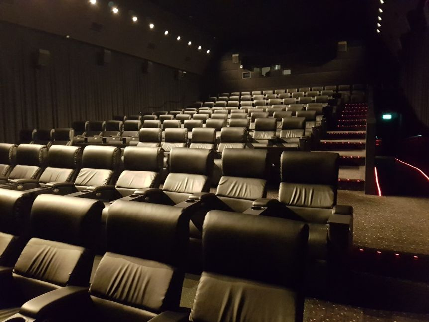 An entirely empty cinema filled with black leather chairs.