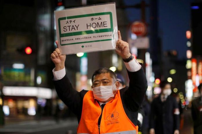 A Japanese man holding a sign that says