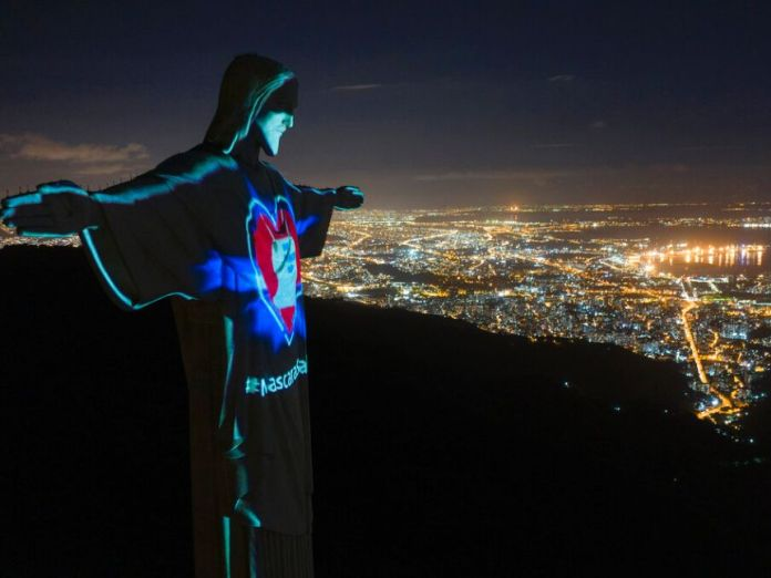You see aerial images of Rio de Janeiro at night with a statue of Christ the Redeemer lit with coronavirus messages.