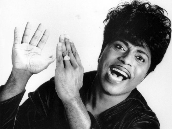 A black and white photo of rock musician Little Richard with his hands about to cheer.