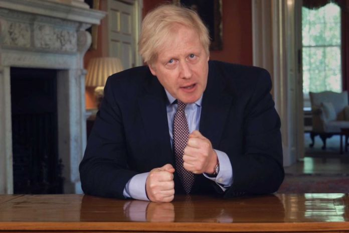 Prime Minister Boris Johnson sits at a table in a dark suit with clenched fists.