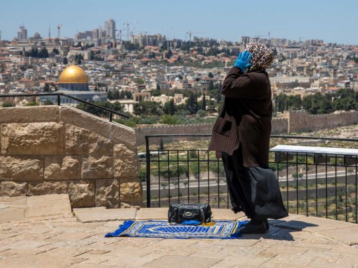 A woman raises her hand to the side of her face as she stands erect while praying at a raised and paved view over the old city.