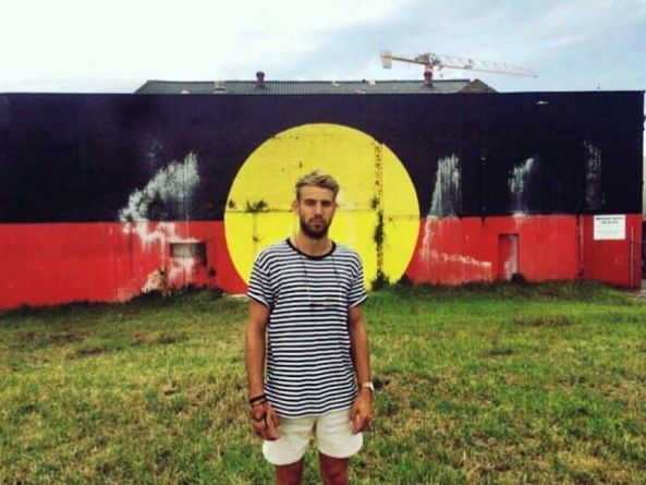 Rulla Kelly-Mansell standing in front of a wall painted like the aboriginal flag
