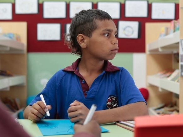 A native boy at a school desk in uniform writing on a piece of paper