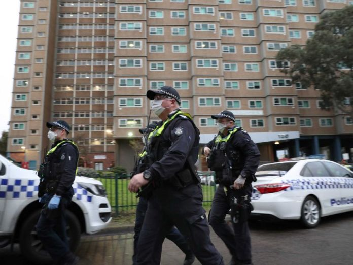Police wearing face masks walk in front of a social housing building.