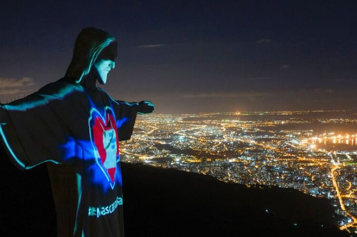 You view an aerial image of Rio de Janeiro at night with the Christ the Redeemer statue lit up with coronavirus messages.