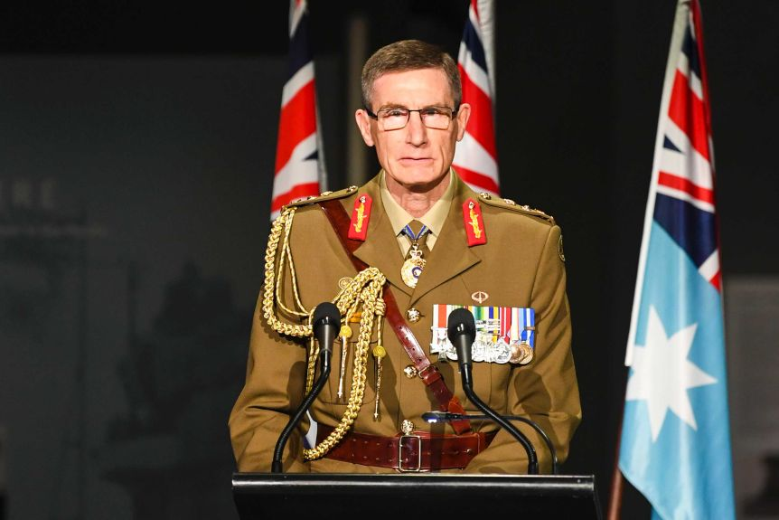 A man in military uniform with medals stands at a podium.