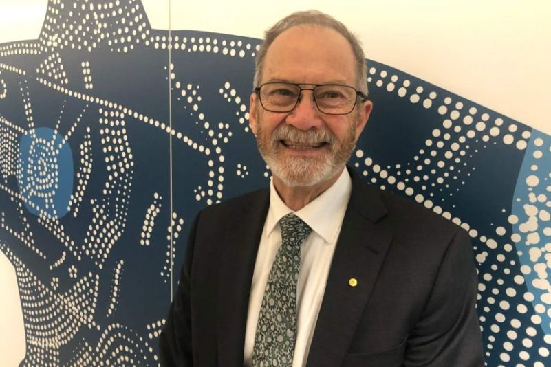 Peter Klinken smiling, wearing a dark suit and white shirt while standing in front of an Indigenous wall painting.